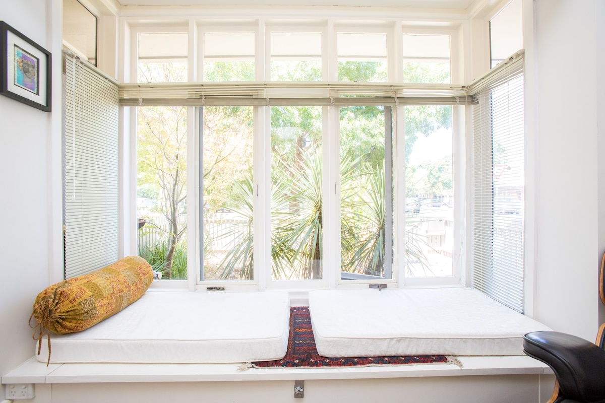 Full double window onto garden view with large bay seating.