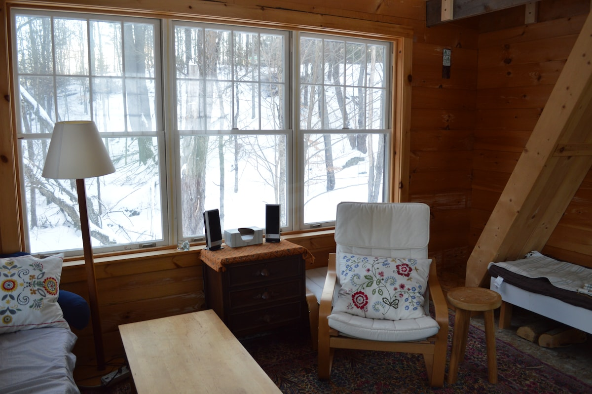 Cabin living room area overlooking brook below.