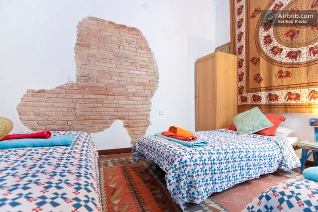 Room 2 with 3 single beds, window and exposed brick