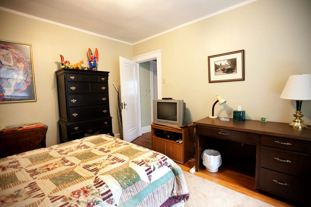 Entrance to bedroom, with tall bureau, TV and desk.