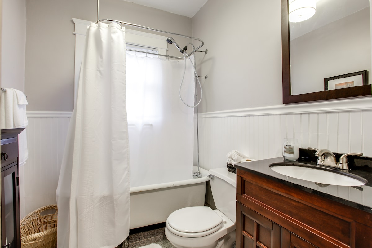 Full bathroom with wainscoting, new granite tile, new vanity, and original clawfoot bathtub with shower combo
