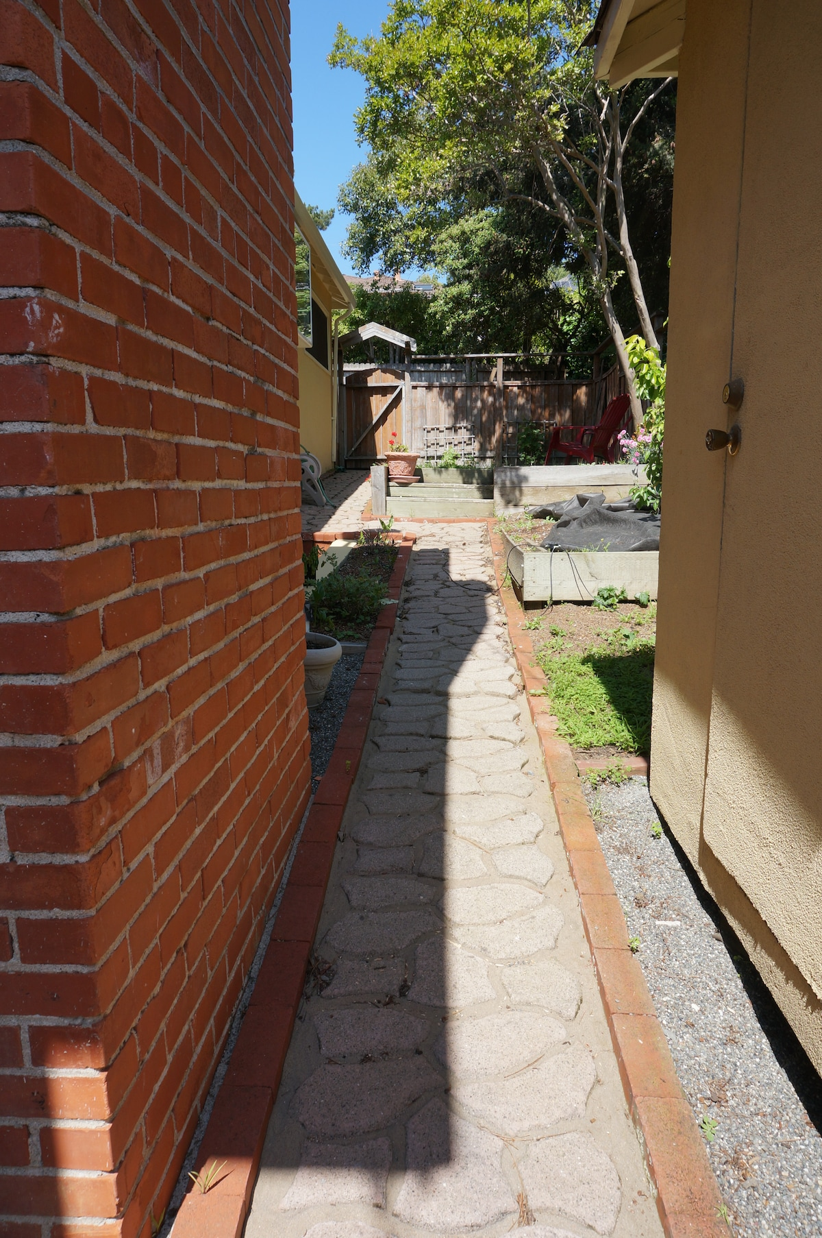 Stone path in private side yard connects from patio to lawn.
