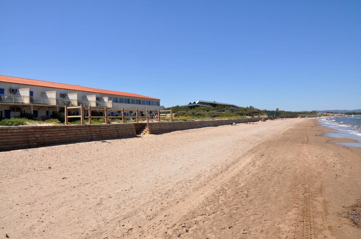 La plage de sable fin en pente douce avec la résidence en fond.
