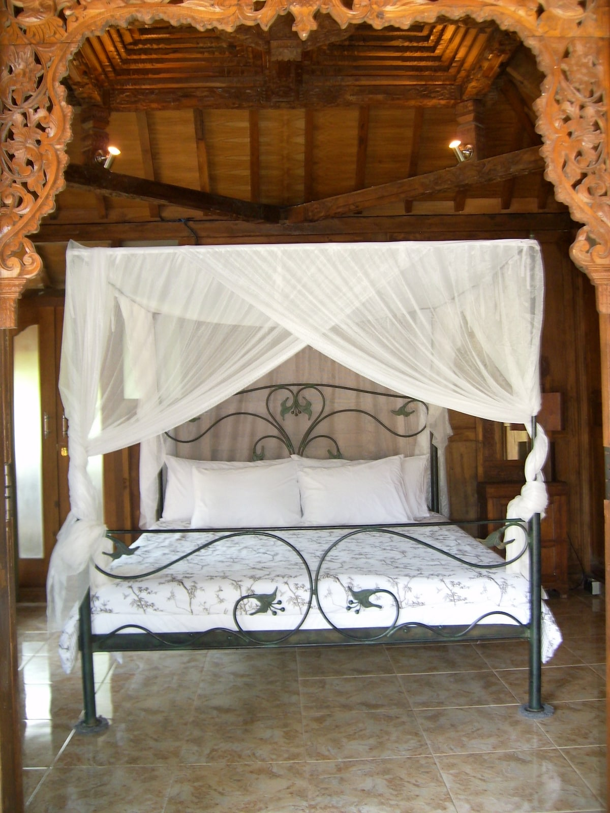The romance of sleeping under a netting...with a beautiful carved ceiling to see in the soft light.