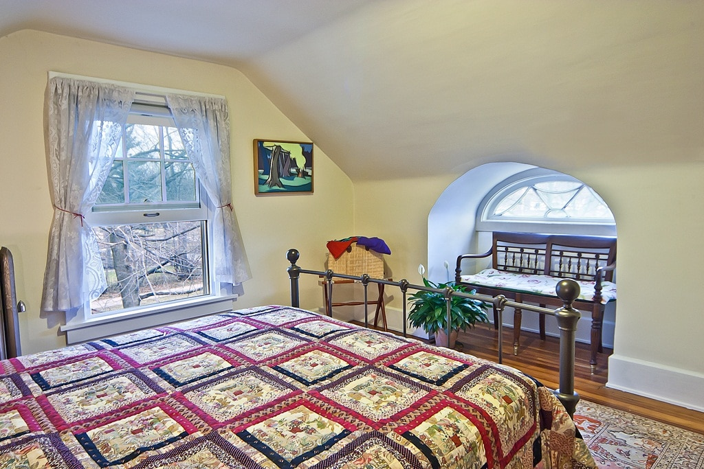 Master bedroom with beautiful eye window, art by artist homeowner, and view of treetops