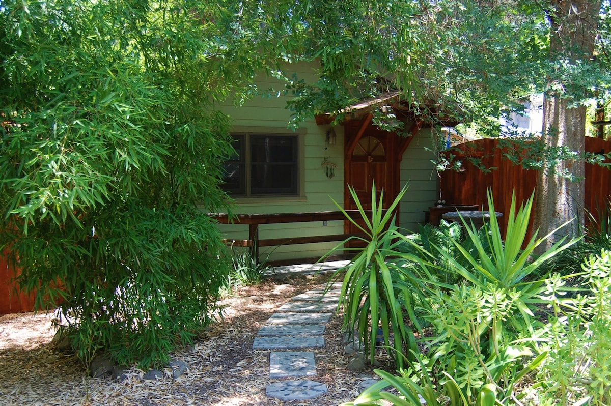 Private entry with many plants and trees. Fully shaded and tropical in feel.