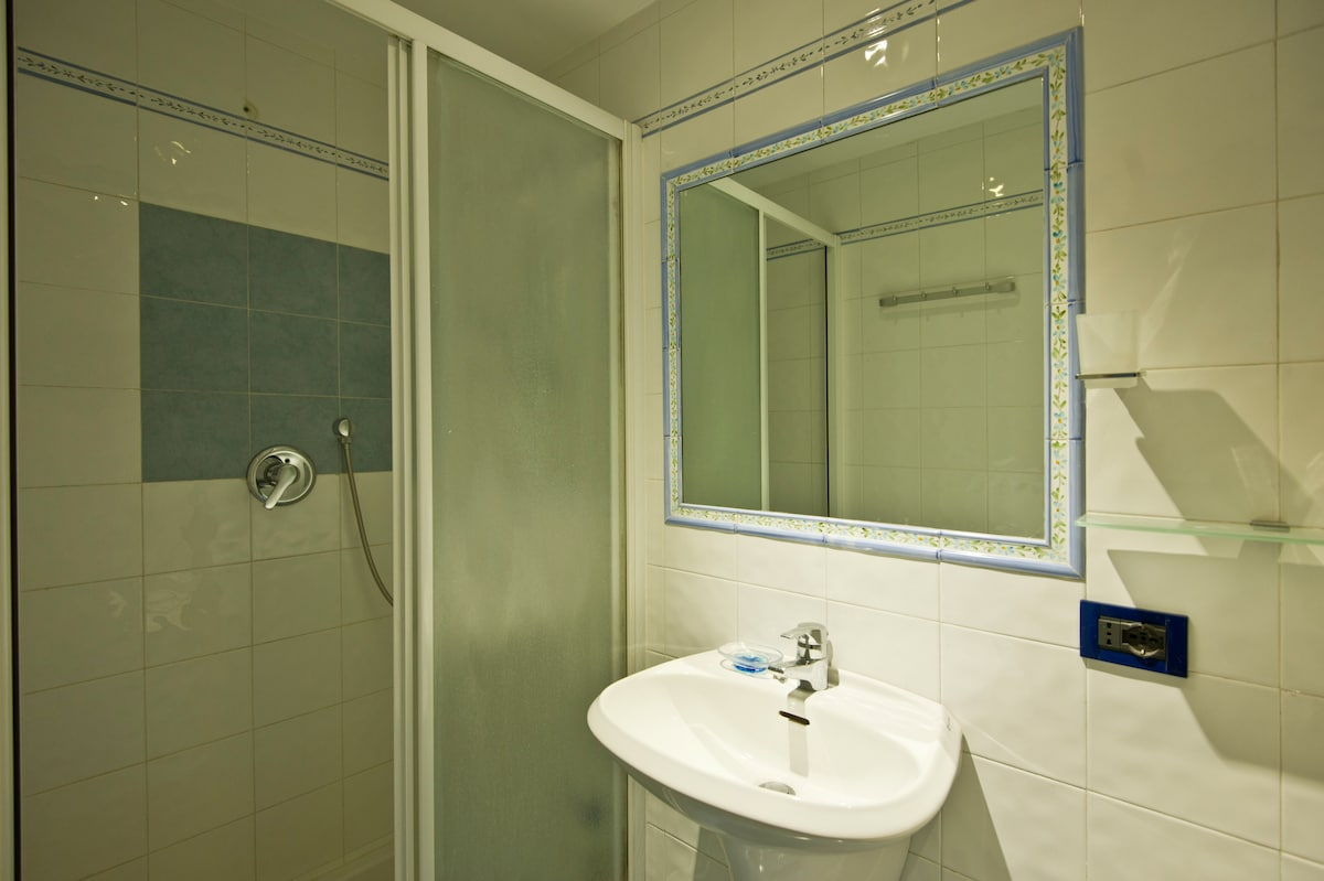 In the bathroom there is a wide shower cabin, an hair-drier, towels, and hot water h24
