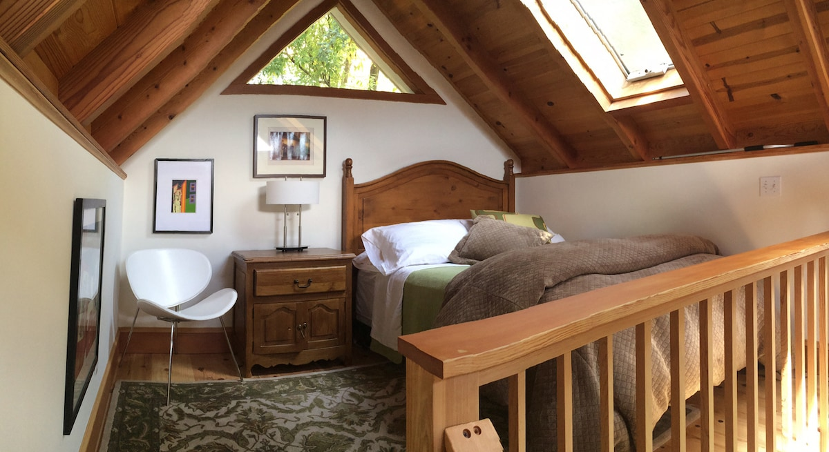 Comfortable full size bed with nightstand up on second floor.