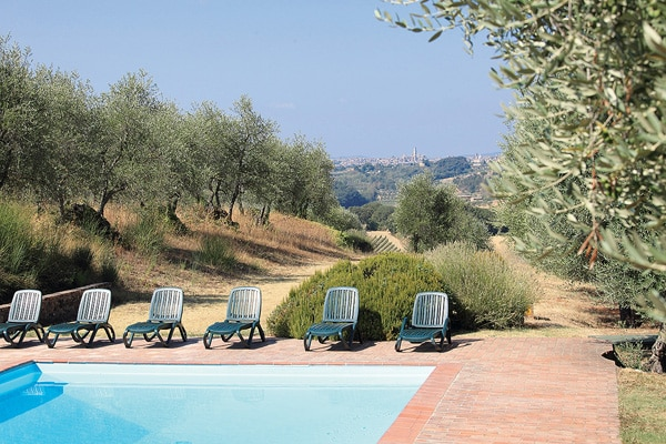 The Pietrina Lodge and Tower Villa pool overlooking the old towers of Siena. Oasis of peace amidst the olive trees