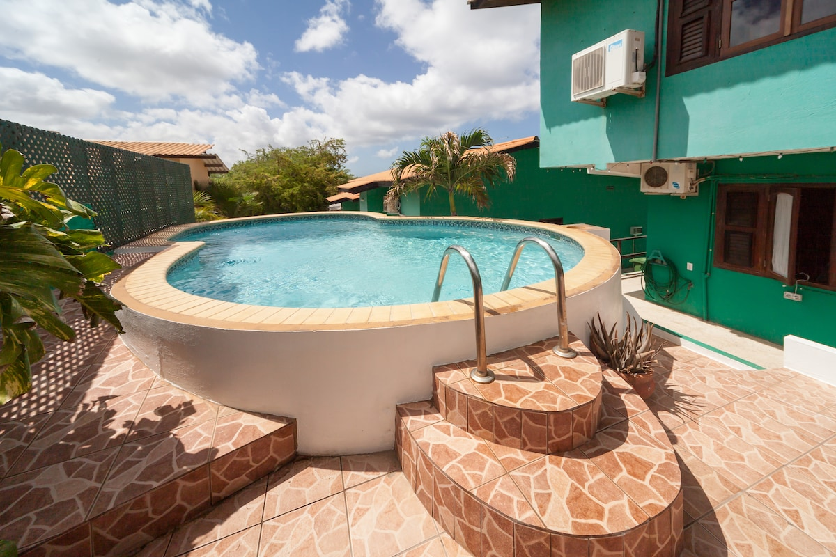 Swimming pool at the back! Enjoy some pleasant and private moments in the shade or step on to the tiled sun terrace with comfortable loungers. Sun terrace and pool are shielded from the road, so pleasant privacy!   Zwembad aan achterzijde met betegeld zon