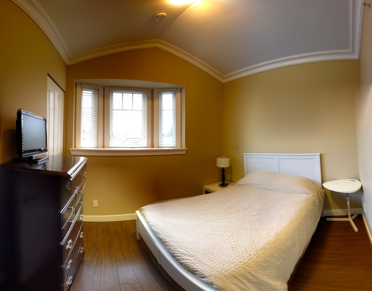 A warm & cozy private room with a comfortable double bed, vaulted ceilings, and a bay window.