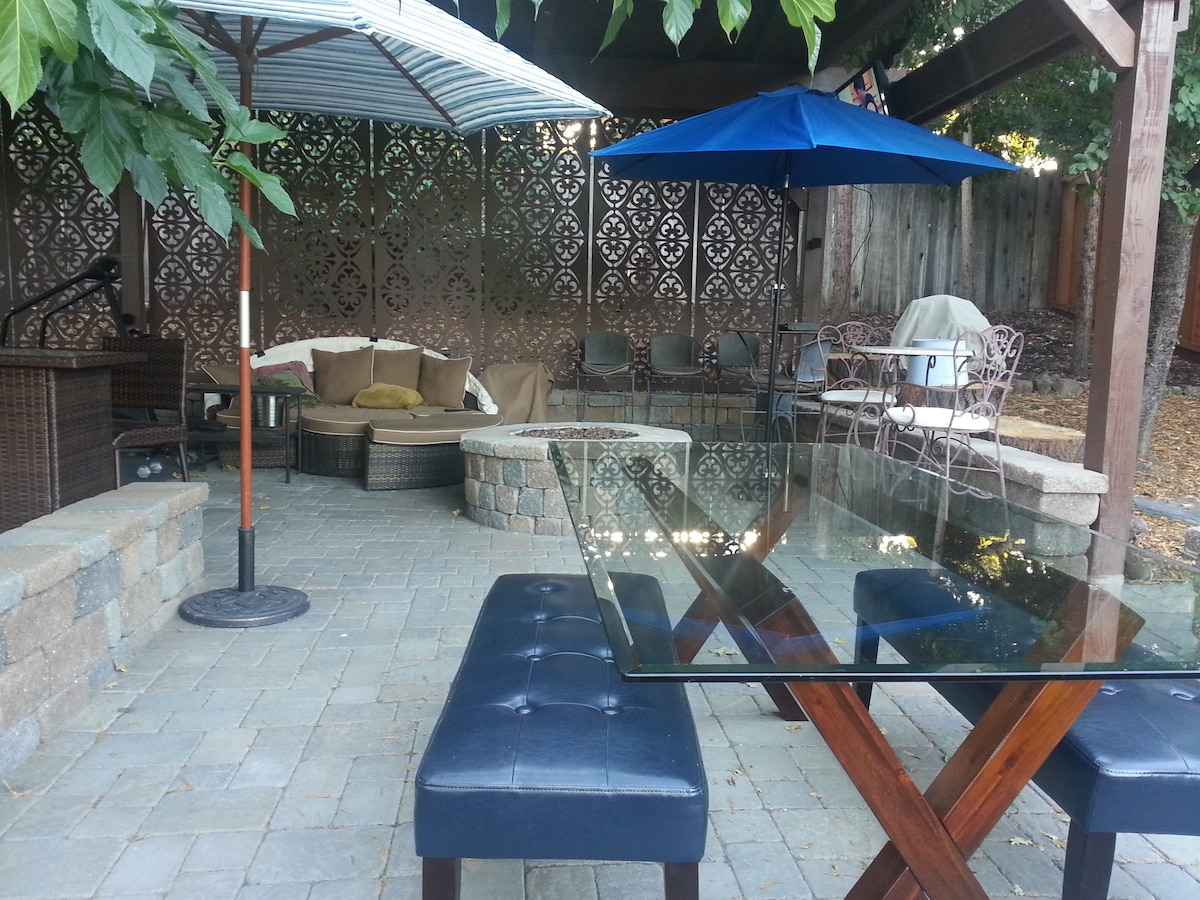 Upper patio with dining table, sofa, umbrellas, firepit and decorative background