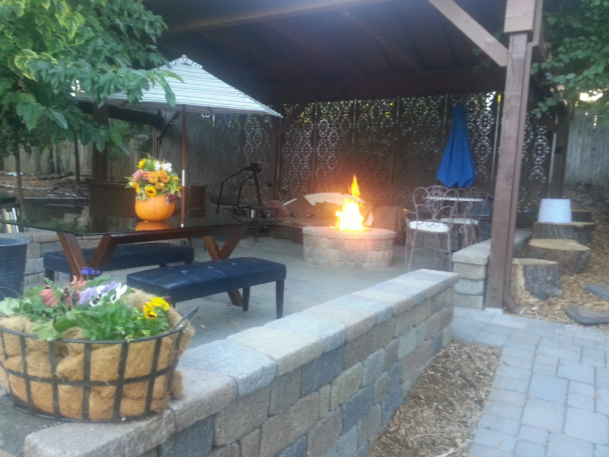 Upper patio with firepit, dining table, umbrellas, and pumpkin centerpiece in the Fall