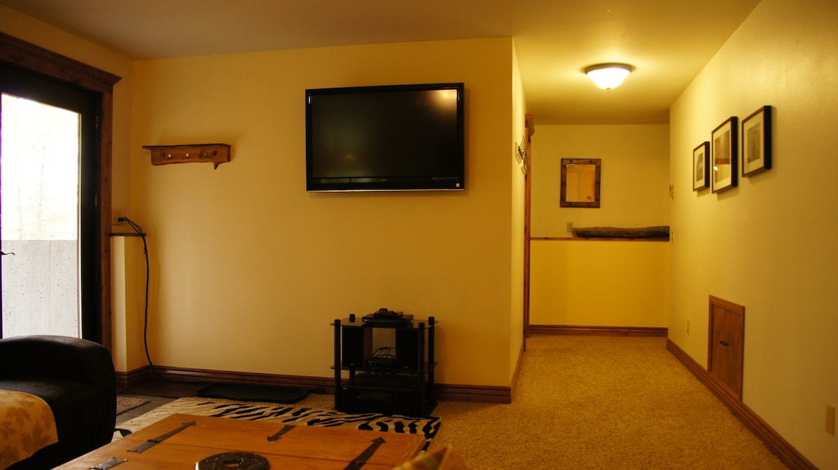 "Your view from the sofa featuring a 42"" flat screen satellite tv, bluray and stereo system, leading into the hallway and the bedrooms."