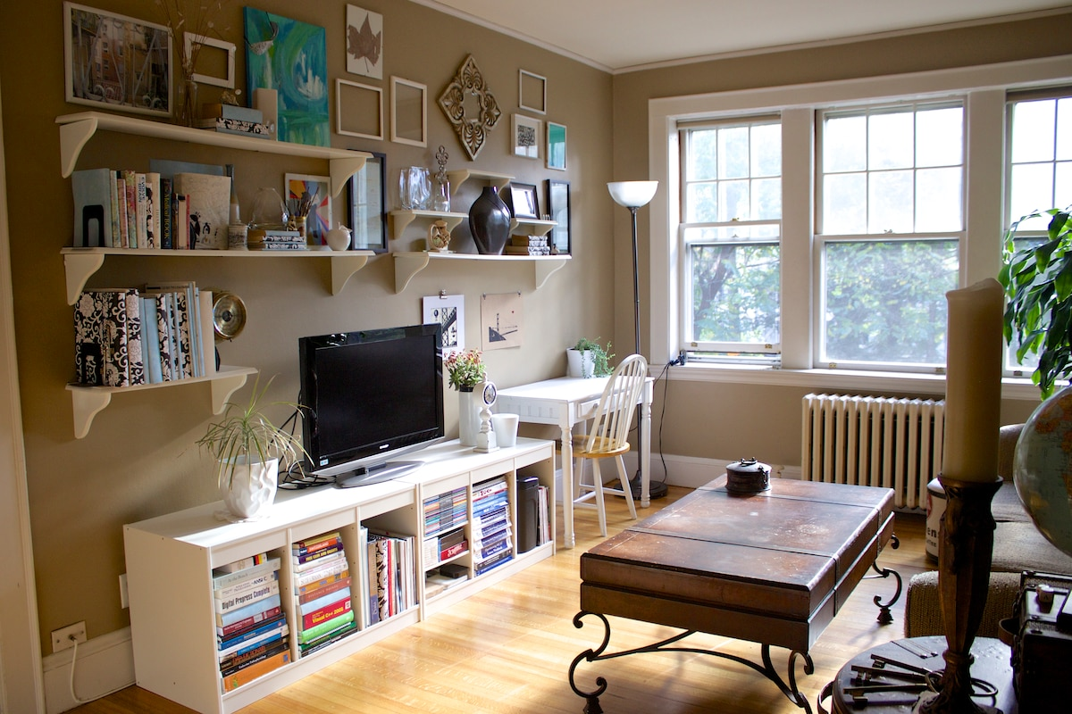 Collection of eclectic art (some hand made) and  books as well as plants and pillows fill the apartment.