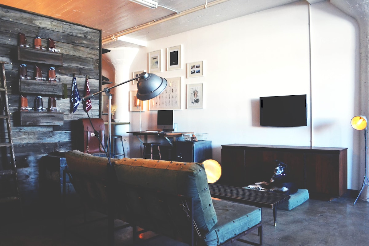 Living room complete with hand-built barn wood wall, Stephen Kenn love seat, and modern walnut credenza | Our loft inncludes Wifi | PS3 | Hulu Plus | Netflix | Amazon Instant