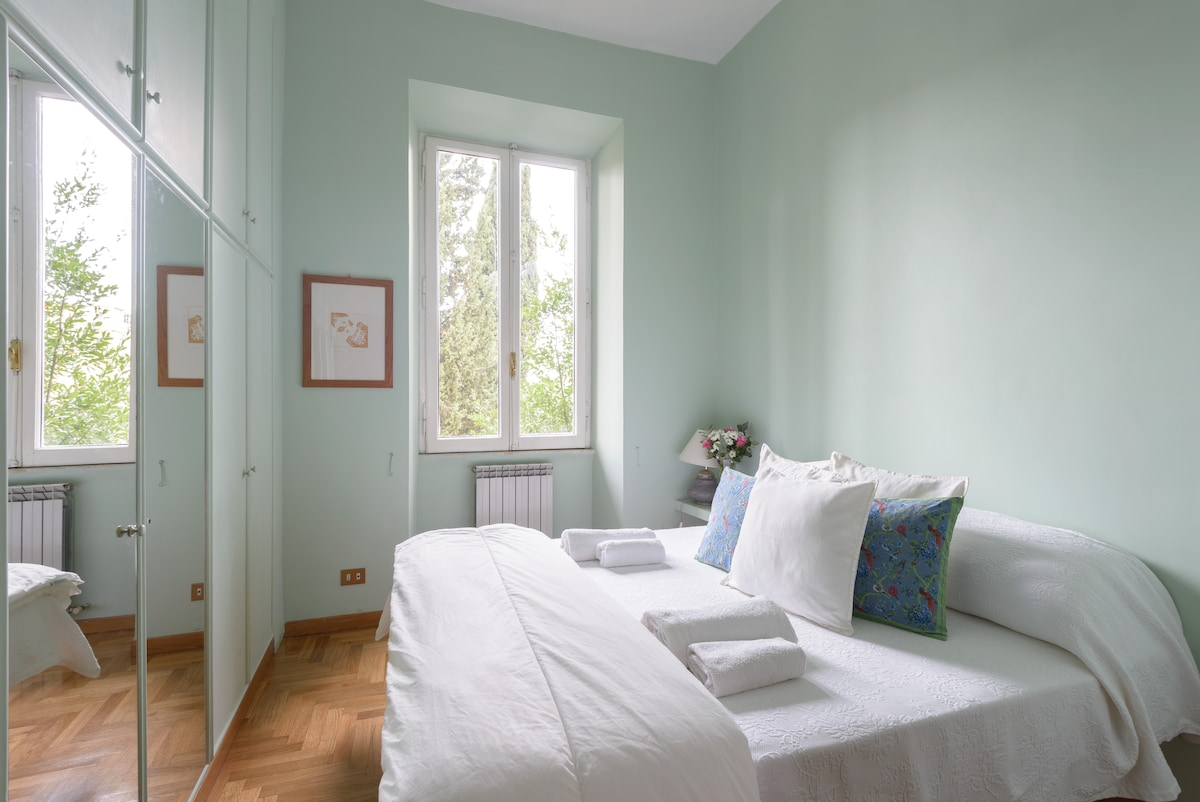 """The master bedroom, also called """"the green room"""" with a double bed and a ceiling fan for sultry summer nights. The room overlooks the gardens of a monastery"""