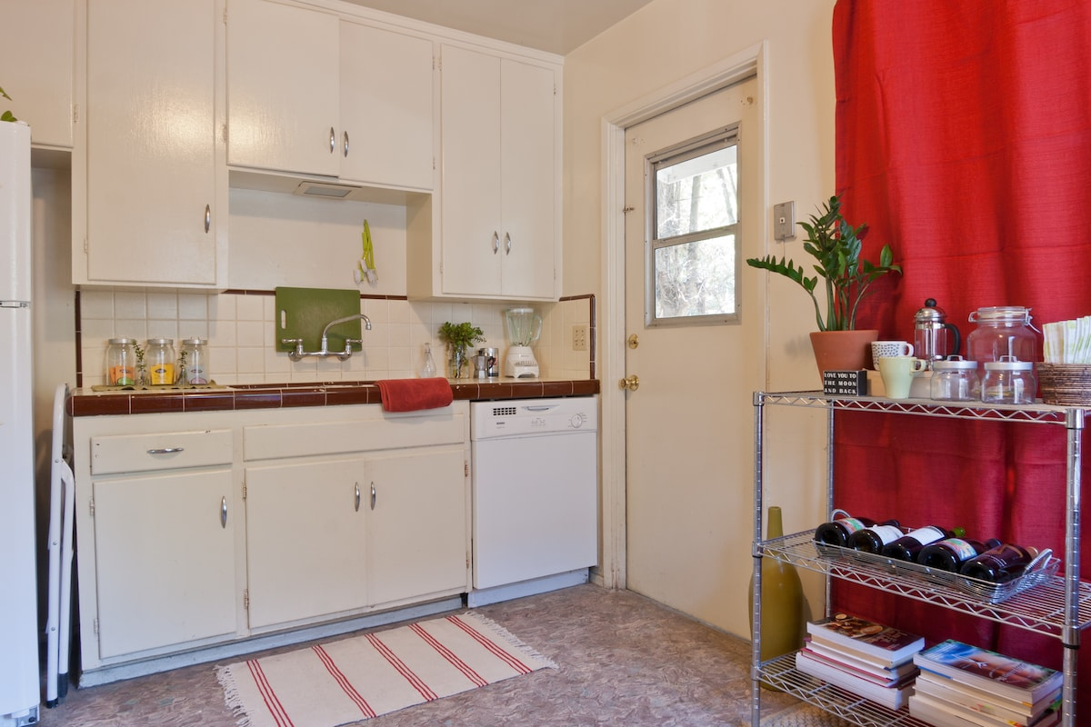 A fully stocked kitchen with a dishwasher, blender, juicer, french press, coffee maker, and stainless cookware!