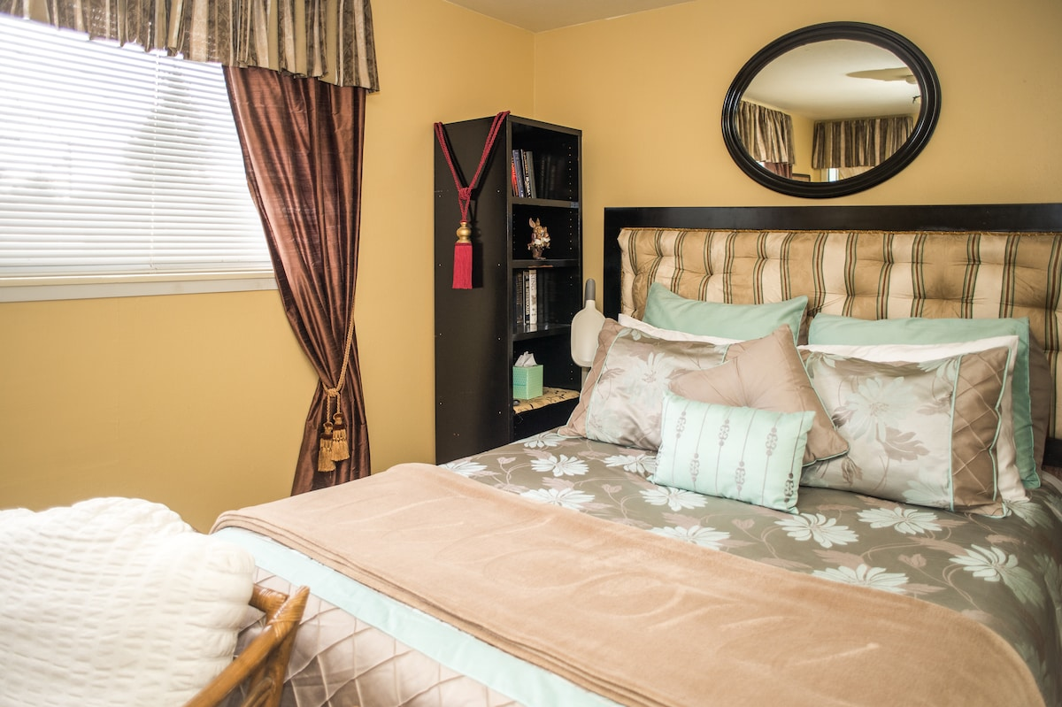 Queen Size Comfy Bed with padded headboard. Bookcase on either side of bed.