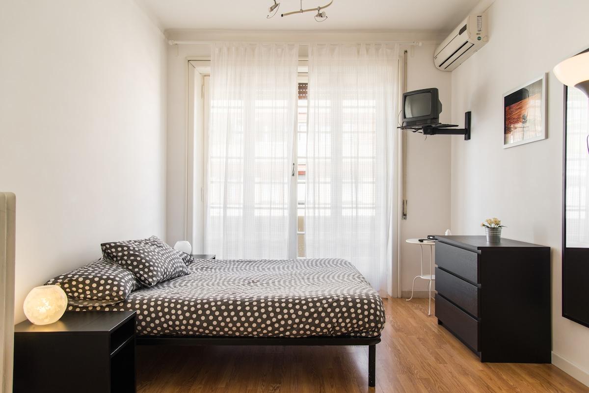 A destra la camera da letto: letto matrimoniale, armadio, cassettiera, scrivania, WIFI, tv, aria condizionata e accesso al balcone con porta finestra
