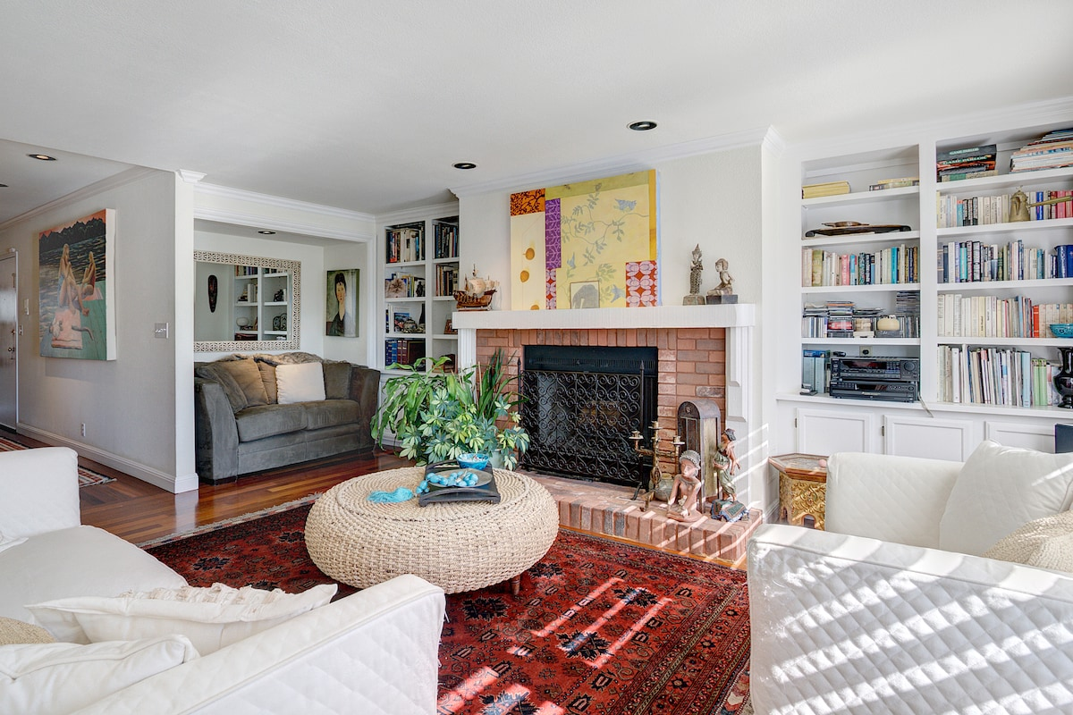 Living room with comfortable sofas and a reading area surrounding the fire place