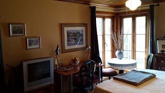 This shows the desk, corner table with large windows overlooking garden (which open for fresh air!)