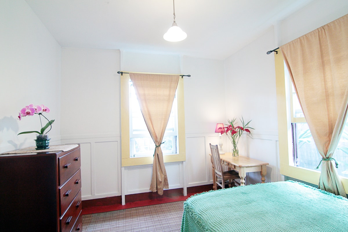 This bedroom features a Hotel double sized bed and views of the garden from the ground level.