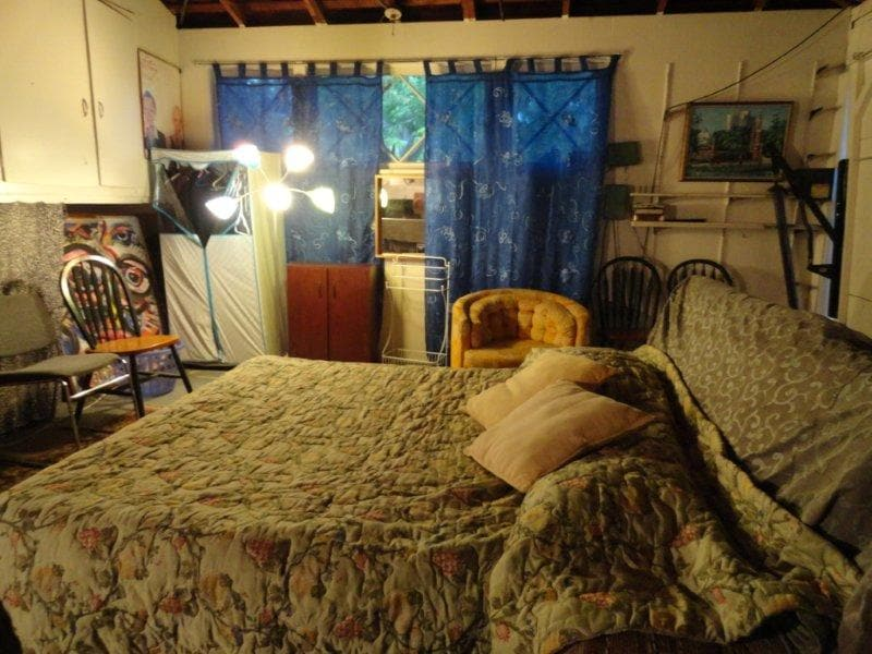 """View of the bed in the little """"nook"""", looking at window and clothes wardrobe"""