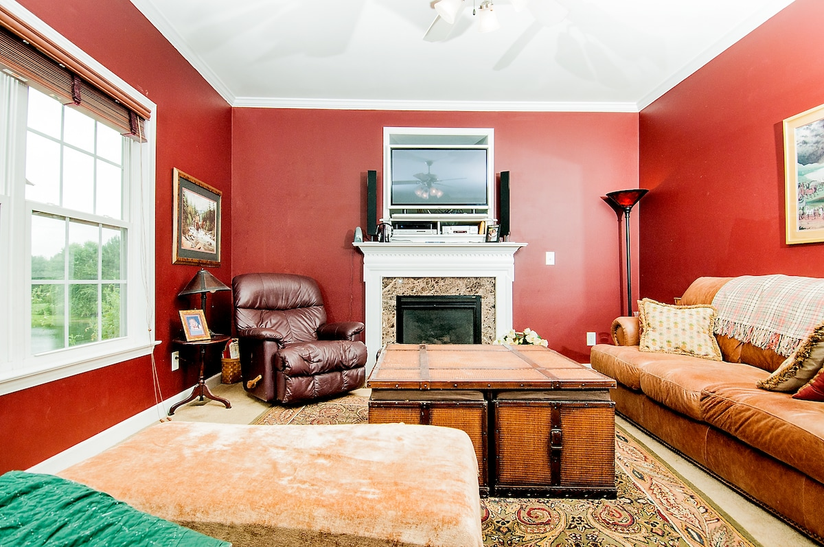 Our living room has comfortable seating with fireplace and television.  There is a view of the pond through the window on the left.