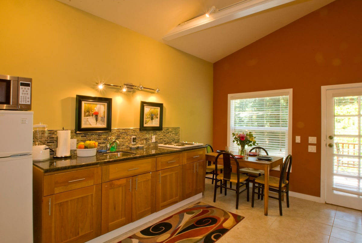 Kitchen has electric stove, microwave, coffee maker, toaster, cookware, and dishes, silverware and glassware for 4