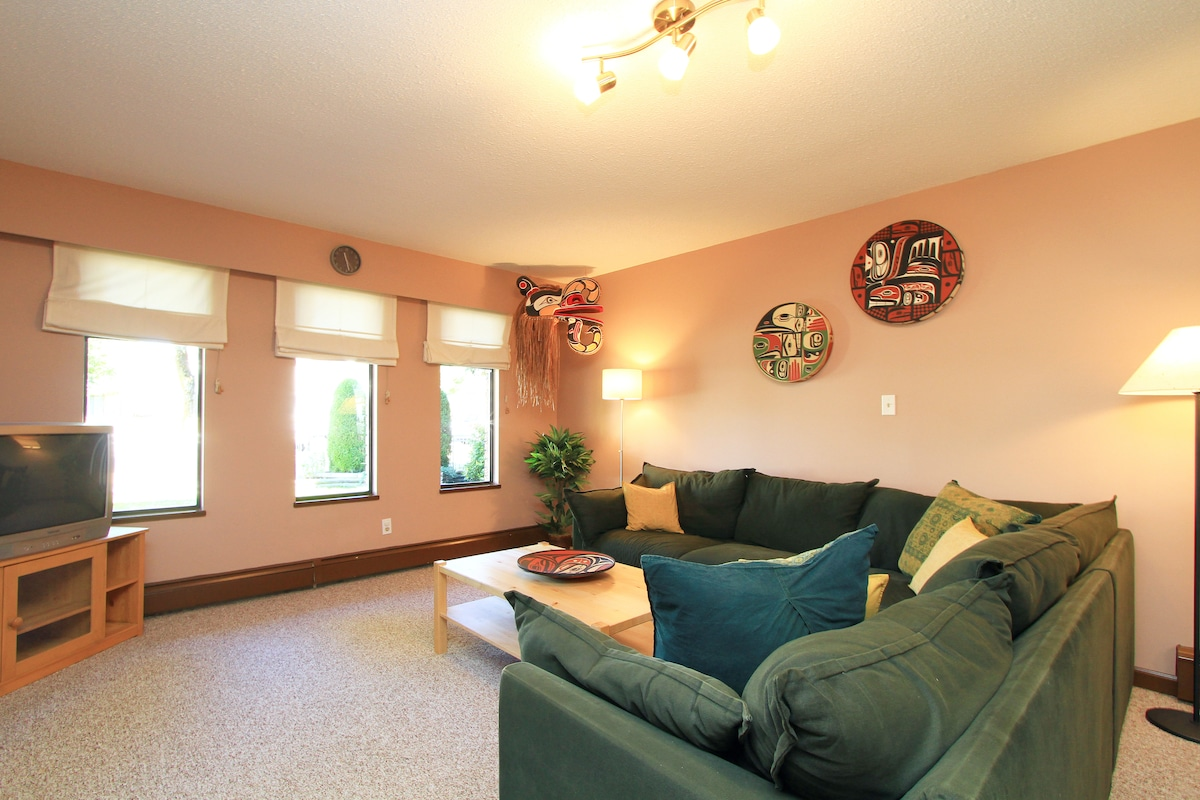 Cozy and comfy spacious living room with large sectional. Decorated  with striking North West Coast Native Art.