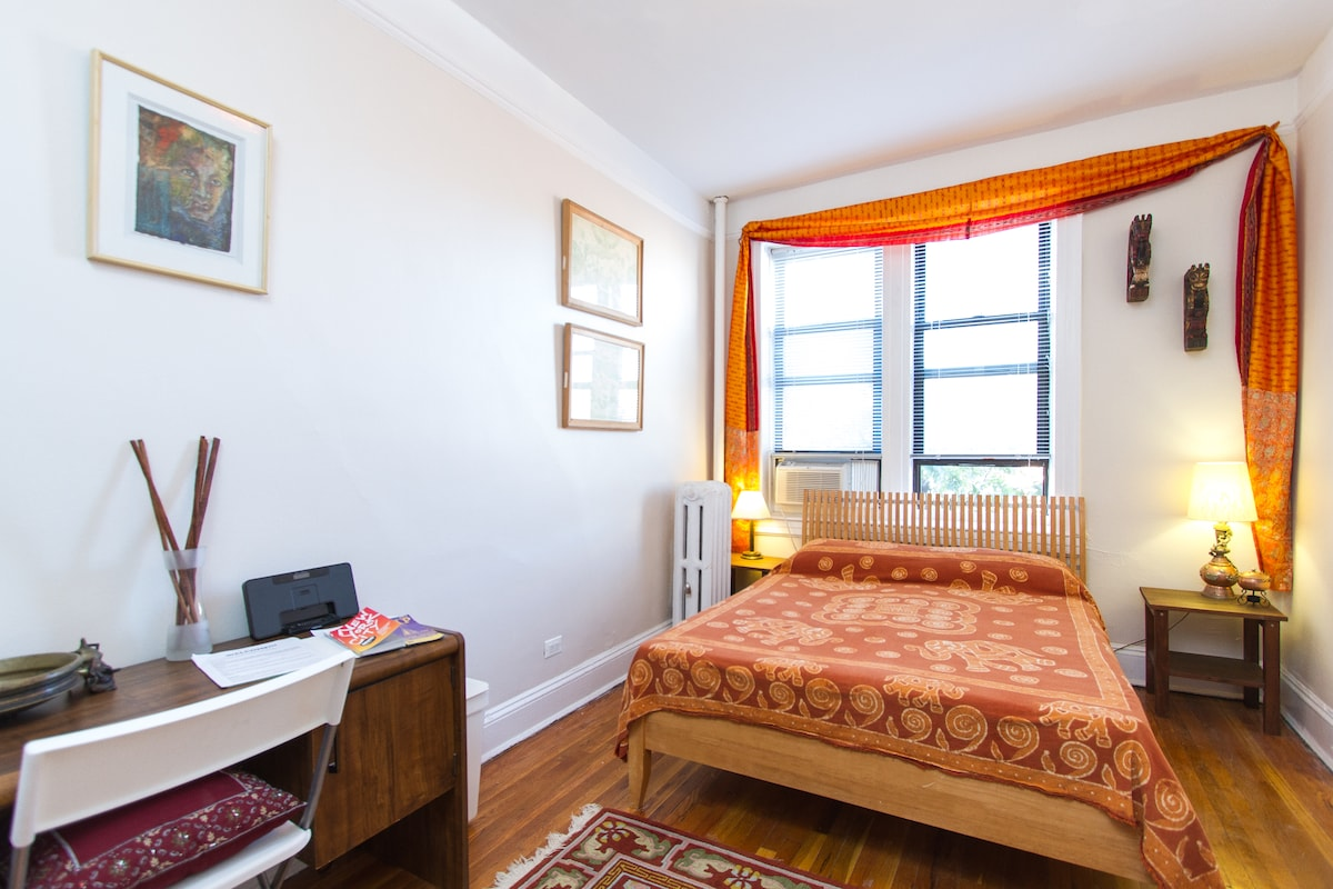 Sunny room with large, queen sized bed and an a/c