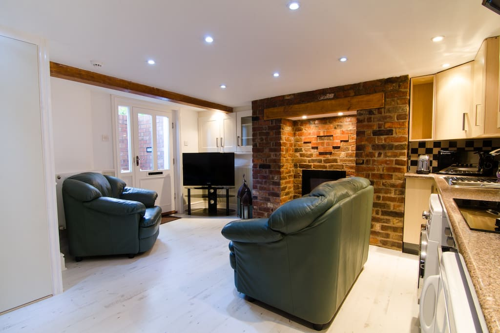 Kitchen/lounge area with large flat screen TV, recessed lighting and smoke alarm