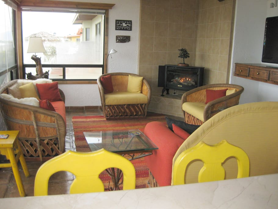The living room has a sofa, two large chairs and a love seat. Panoramic views. Warm colors.