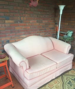 Love seat on screened in porch