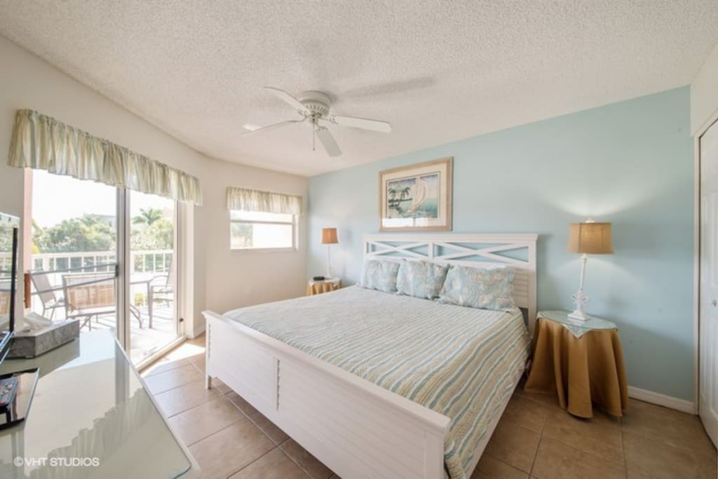 The master bedroom features a king bed, television, and access to the patio.