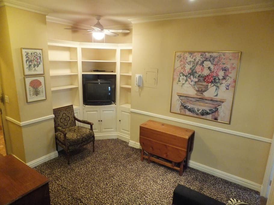 Sitting room has microwave, toaster, coffee maker, mini-fridge, folding-leaf dining table, 2 arm chairs, 3 folding TV tables, cabinets/shelves and large closet.
