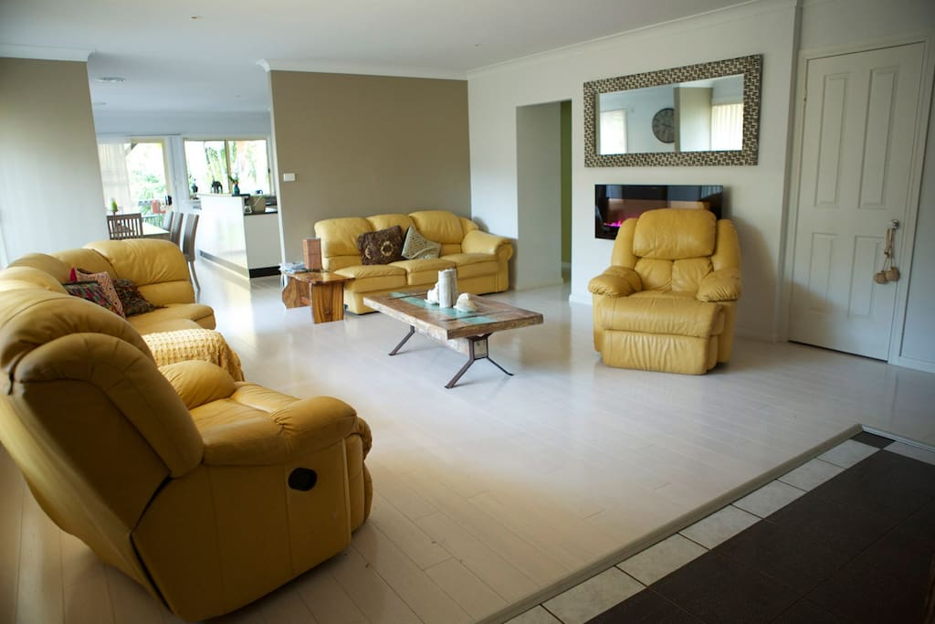 Large Living area, featuring polished white washed floors and a contemporary beach chic feel.