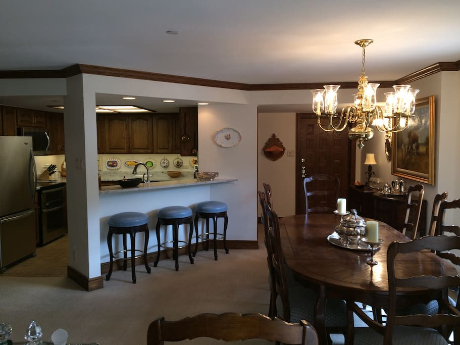 Kitchen on the left. Entrance door and dining table that can sit 10