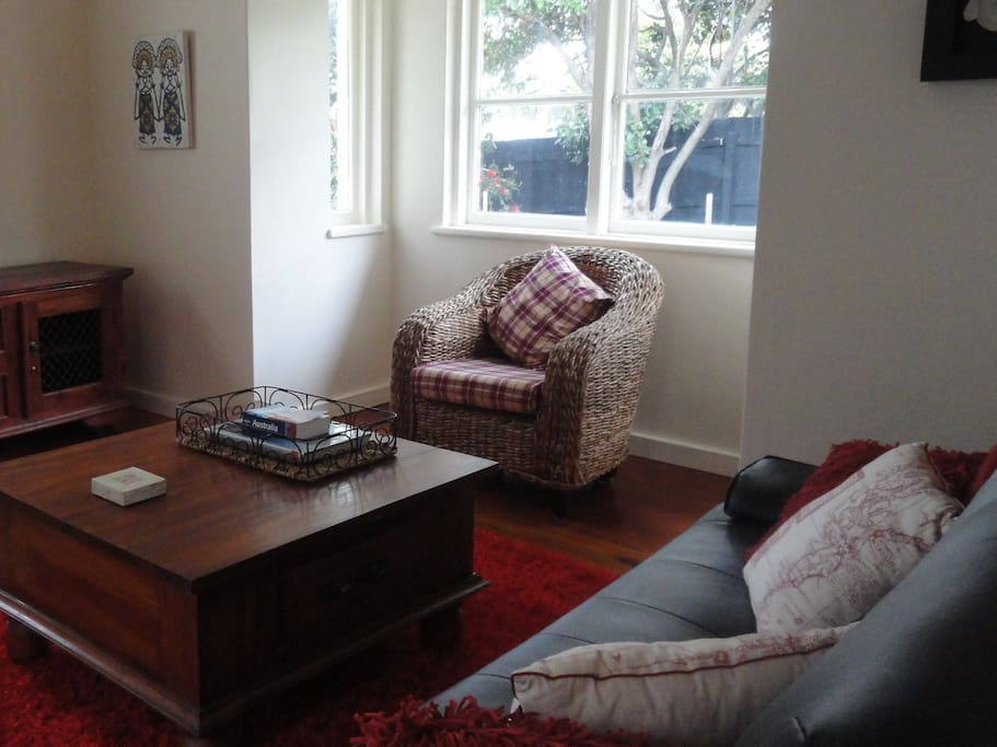 Living room with sofa that converts to a double bed, dining area with books and DVDs
