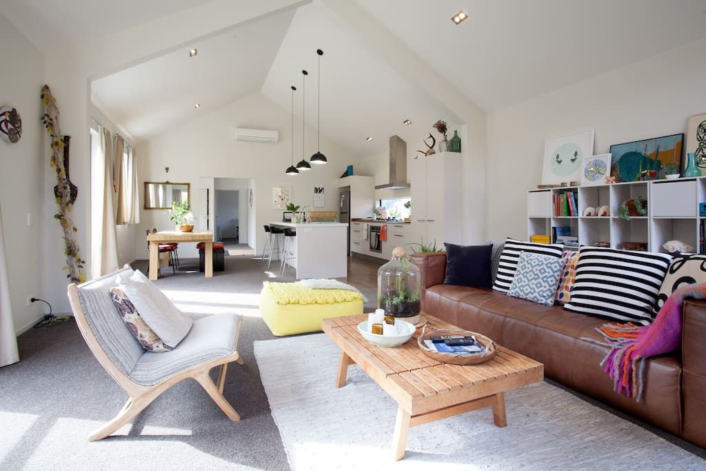 Shared living space, comfy leather couch, open and light filled open-plan living area.