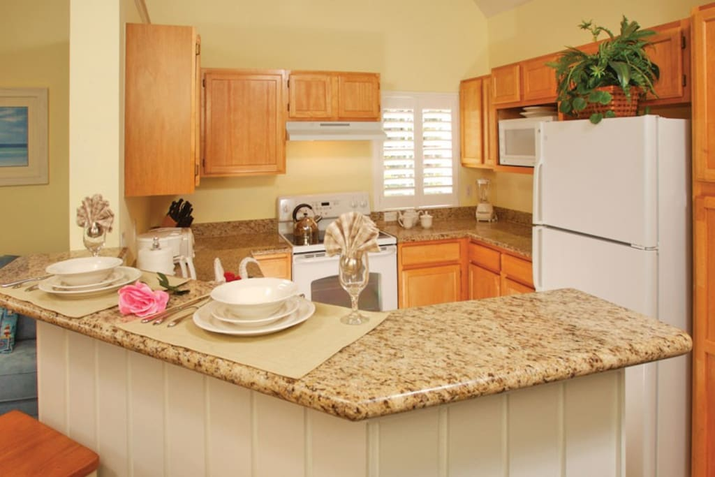 Kitchen with full size refrigerator, full size oven/range, full size dishwaher, dishes, cups, silverware and Breakfast Bar