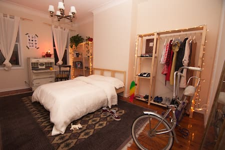 The apt is on McGolrick Park. The room is quite charming and ample, with a comfy bed, a vintage secretary, and beautiful views to the backyards, great natural light year round. Close to bars, eateries, shops, and subways. Easy access to Manhattan.