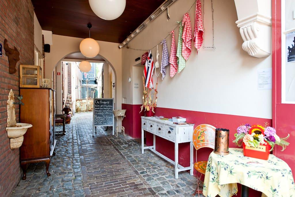 De cour. Met de entrée van de brasserie en achteraan rechts de trap op naar de suite..