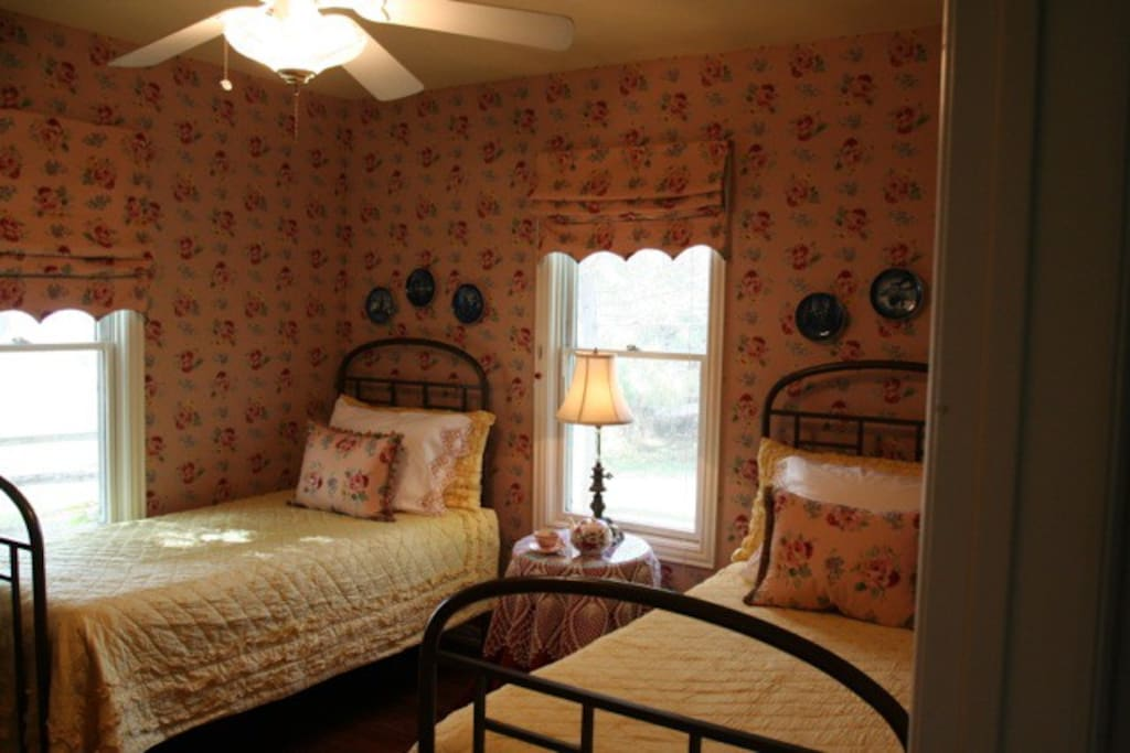 Antique twin brass beds in a beautiful and comfortable room with hardwood floors
