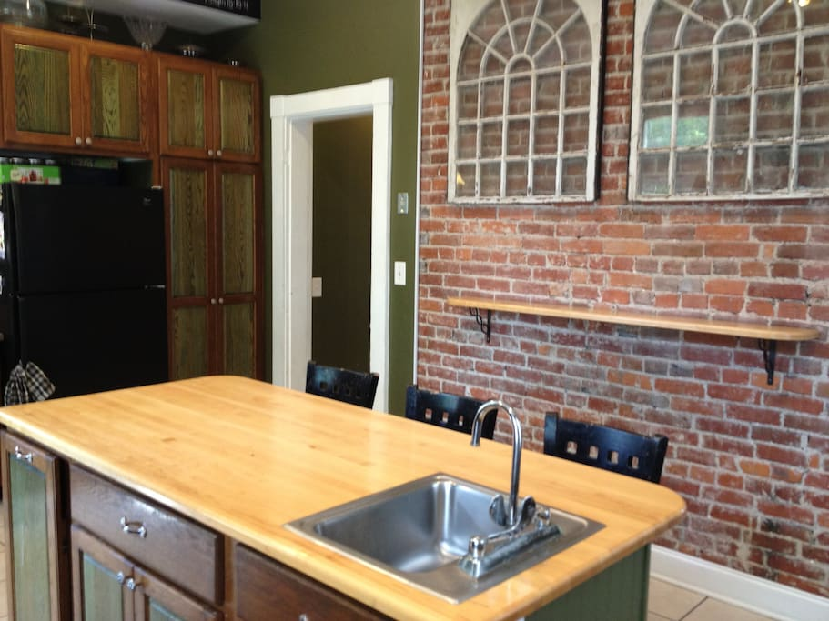 Large kitchen with an island with seating, exposed brick, built in gas stove, beer tap and lots of natural light.