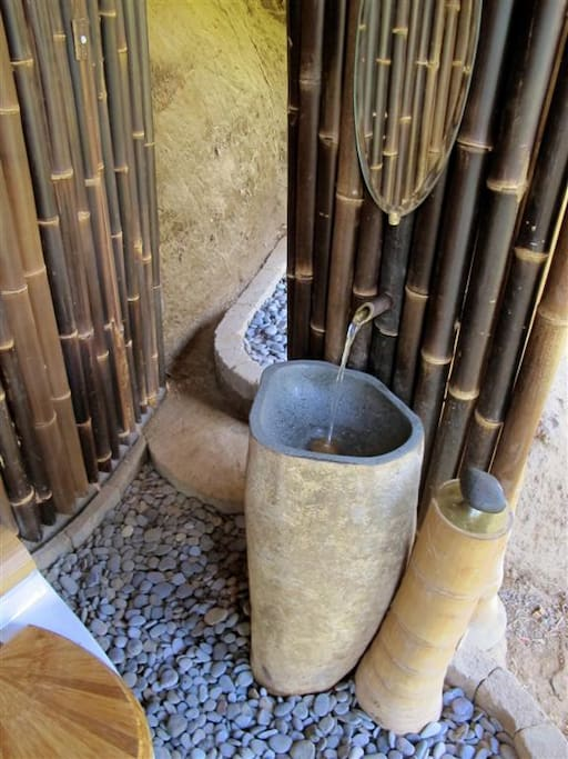 Stone Wash basin with bamboo pipe as tap underneath the house