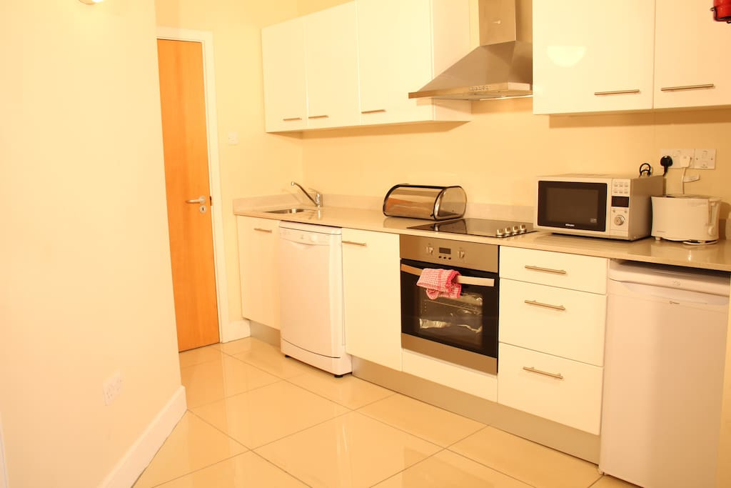 Kitchen with door to small utility room where washing machine is housed.