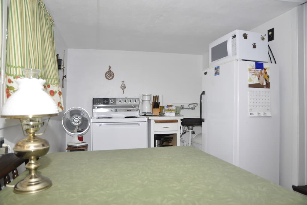 Kitchen with full range, refrigerator and microwave; kitchen utensils provided.