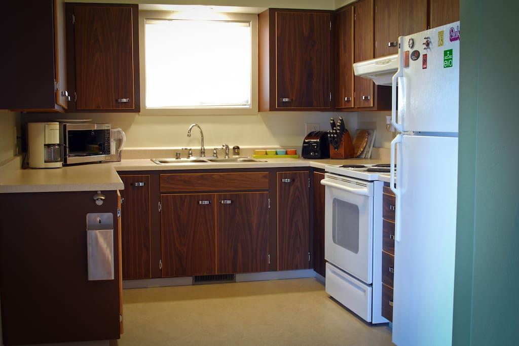 Fully stocked kitchen w/ new walnut cabinet doors and marmoleum flooring.